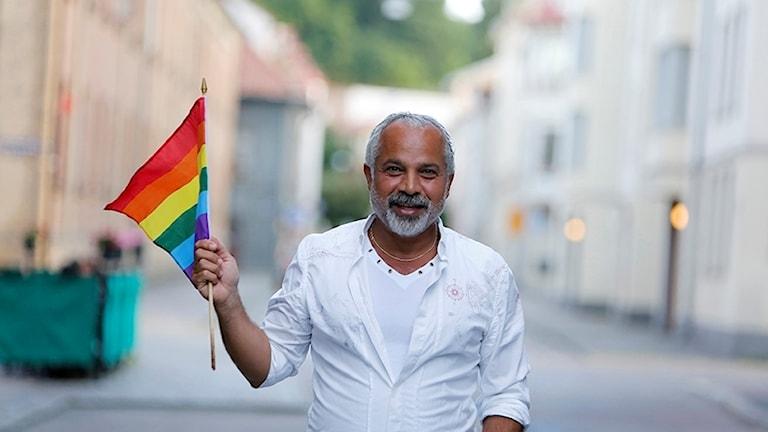 Ardeshir Bibakabadi med en Regnbågsflagga