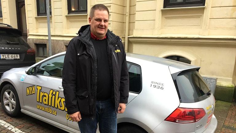 """Kjell Pohlin står utomhus iklädd en svart täckjacka, framför en liten grå bil. På bilen står det """"Nya trafikskolan"""" i gul text."""