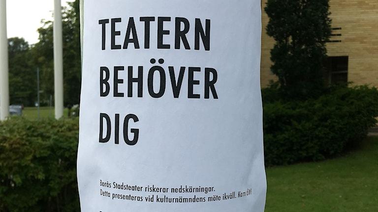 Ett papper har tejpats på en stolpe med texten: Teatern behöver dig. Borås Stadsteater riskerar nedskärningar. Detta presenteras vid kulturnämndens möte ikväll. Kom dit!