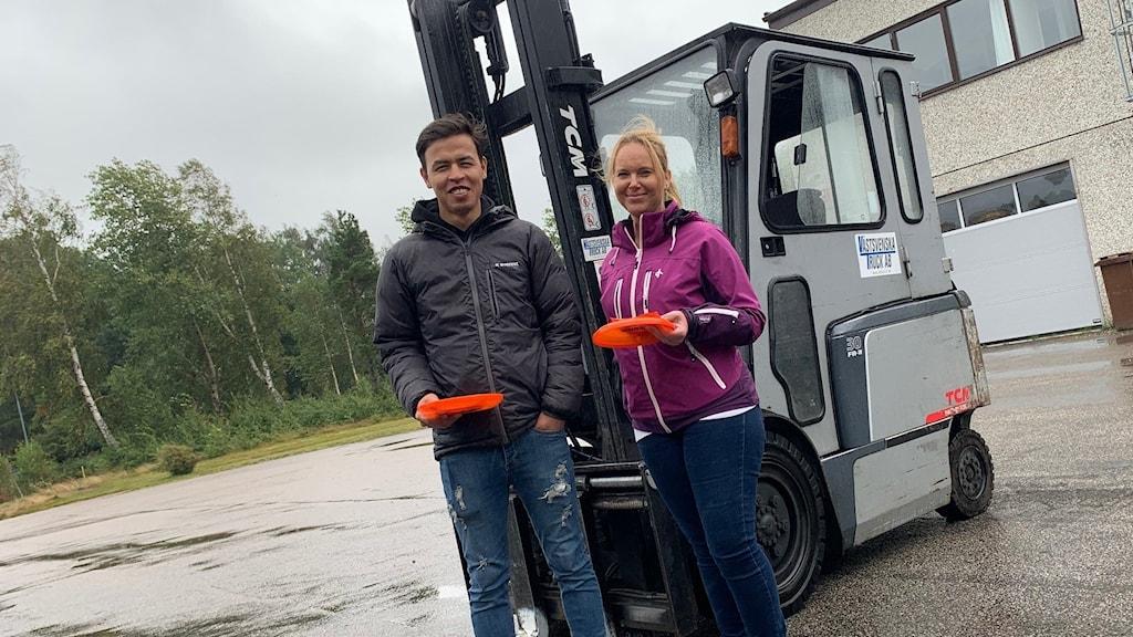 En man och en kvinna ståendes framför en truck.