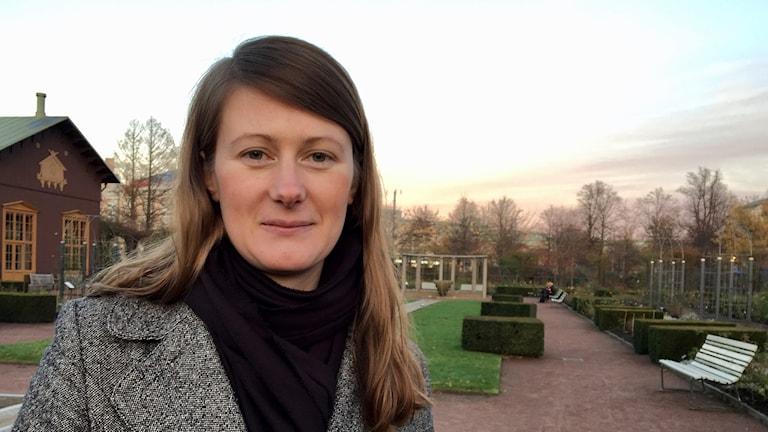 Profilbild på Lise Nordin. Hon har en kappa och står i en park.