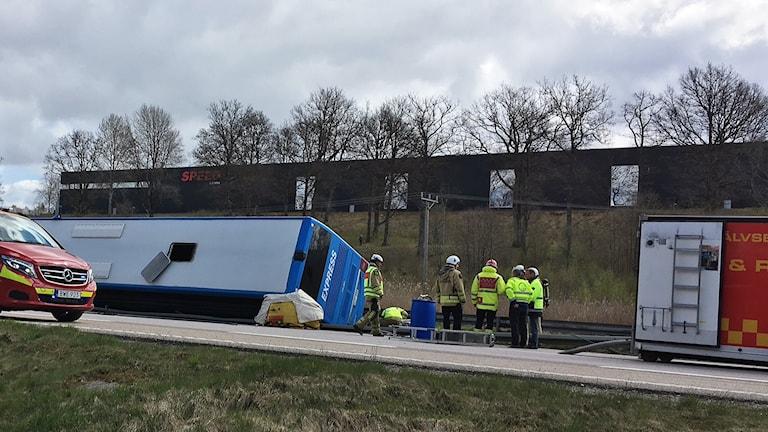 Räddningstjänsten arbetar kring den liggande blå bussen.