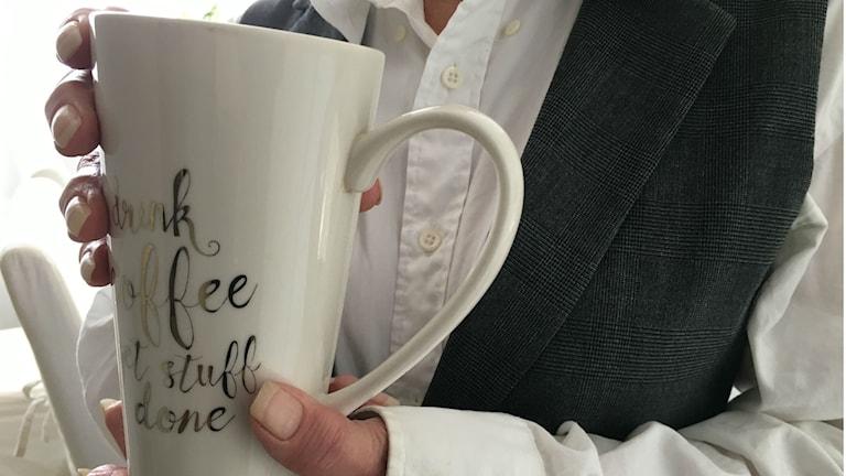 En kvinna håller i en kaffekopp.