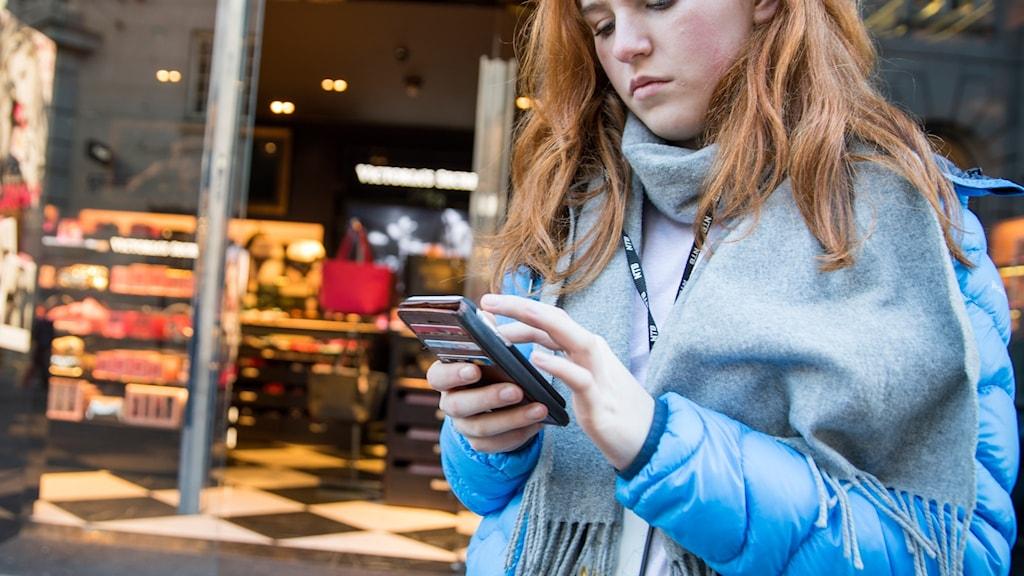 Tonåring med mobil utanför butik