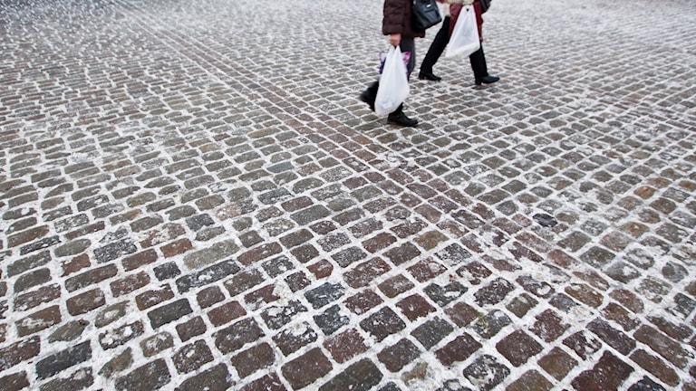 Personer går på frusen gatsten.