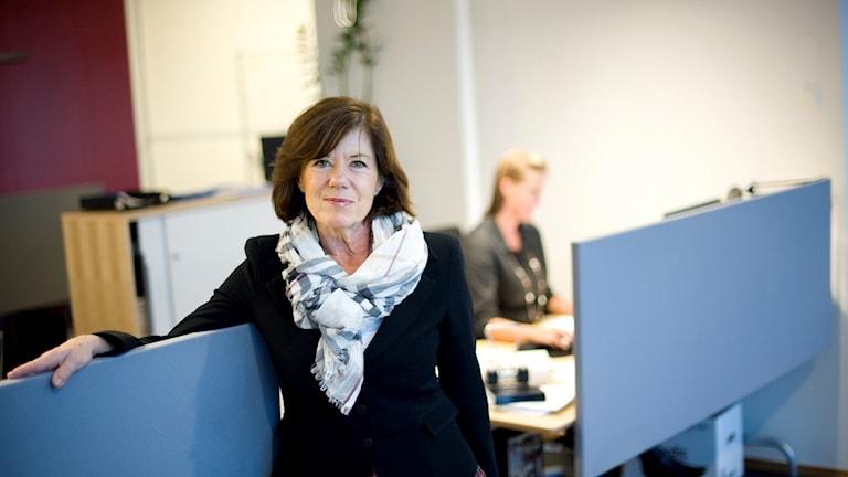 Lena Apler har kavaj och stor sjal och ser glad ut, hon står i en kontorsmiljö.