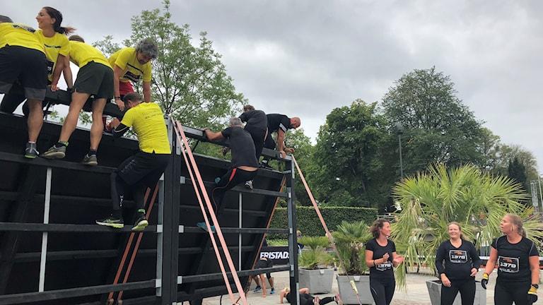 Flera deltagare hjälper varandra över ett hinder under Borås Action Run