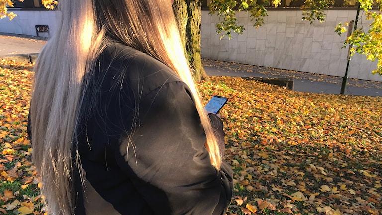 En kvinna med blont hår står med en mobil i handen.