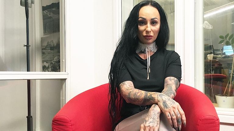 En kvinna med svartfärgat långt hår och svart t-shirt, sitter i en röd fotölj. Hennes armar och händer är tatuerade.