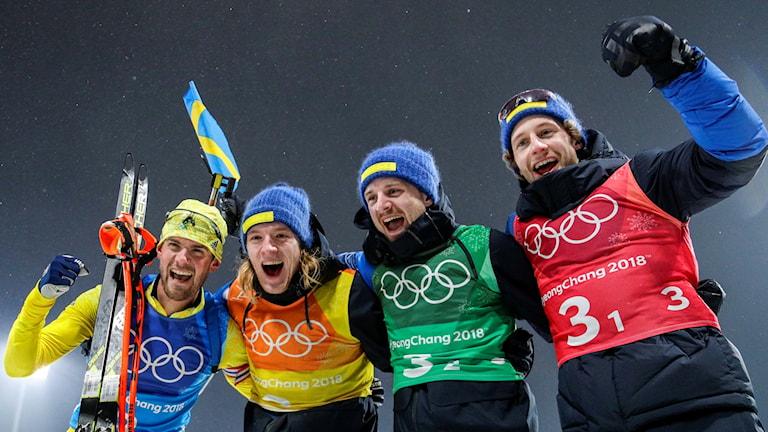 De fyra lagåkarna i herrstafetten i skidskytte är iklädda tjocka vinterjackor och blå mössor och skriker ut sin glädje mot kamerorna efter OS-guldet.