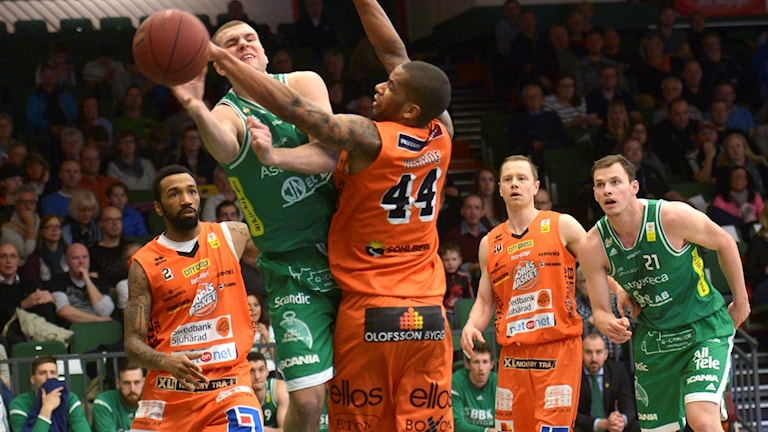 Basketspelare i orange respektive gröna dräkter fajtas om bollen.
