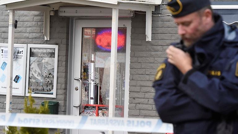 En polis står utanför butiken där glasrutan i dörren krossats.
