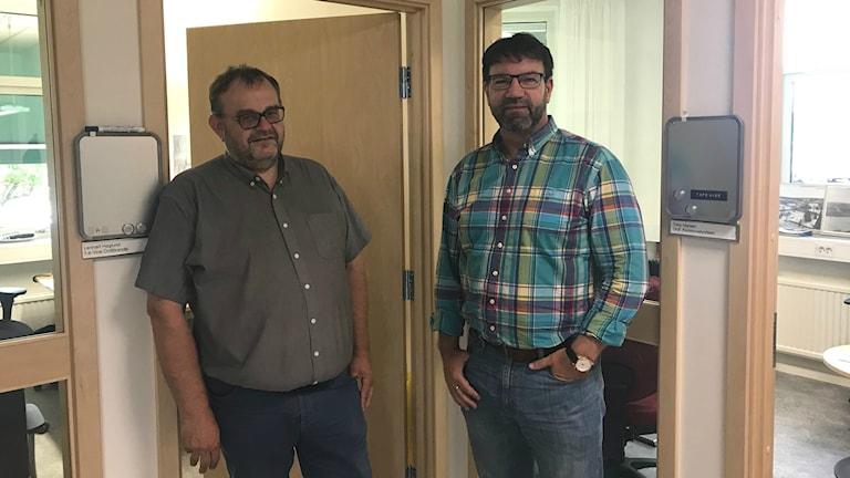 Två män står bredvid varandra utanför sina kontor.