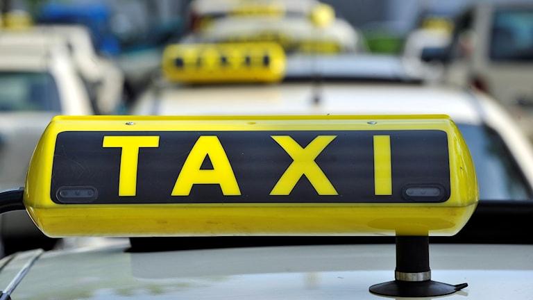 En taxiskylt syns i förgrunden, bakom står flera andra taxibilar.