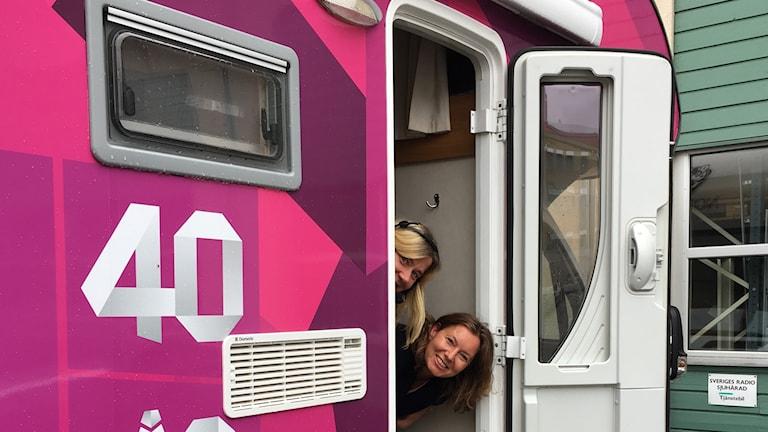 Kristin Holmberg och Sara Kvist sticker ut sina huvuden ur dörren till sändningsbussen.