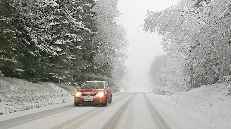 En bil kör på en snöig väg.