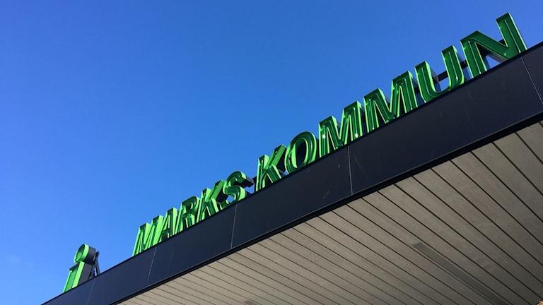 """""""Marks kommun""""i gröna bokstäver tvärs över hela bilden, från vänster till höger. Bokstäverna är på ett svart tak, vid entrén till Marks kommunhus. Bakom bokstäverna en klarblå himmel."""