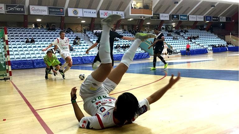 En man ligger på golvet i en inomhushall nära kameran. I bakgrunden pågår matchen.