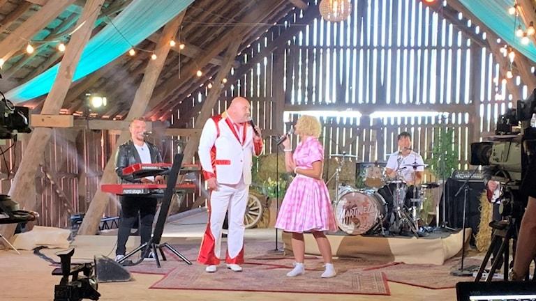 På en loge spelar SVT in med flera kameror riktade mot dansbandet Martinez som gästas av Peter Larsson från Lars-Kristerz, han är klädd i vit kostym med röda detaljer. Sångerskan har rosa klänning med vita prickar. Klaviaturspelaren har svart skinnjacka och trummisen vit T-shirt. Solljuset sirlar in mellan springorna i laduväggen.