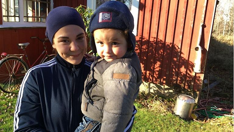 Marilyn håller sonen Emilio i famnen, utanför deras hus.