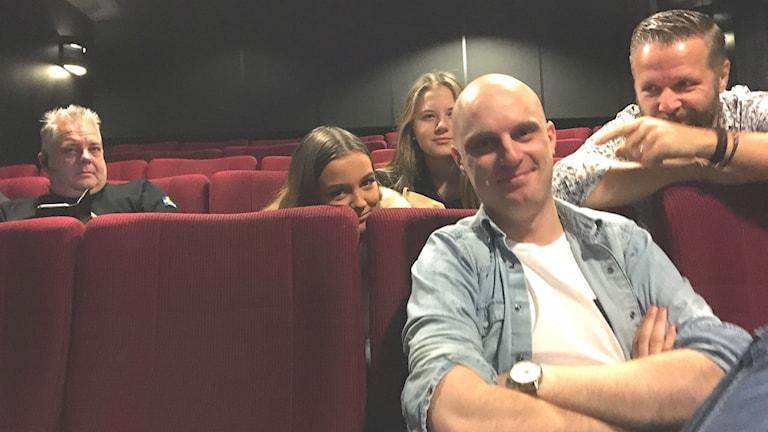 Linus Karlsson i en röd biosal tillsammans med några skådespelare i bakgrunden.