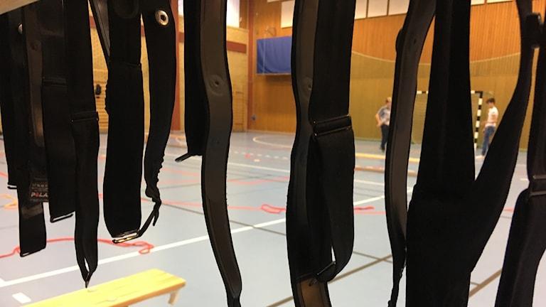 Flera pulsband hänger inne i en idrottshall med blått golv.