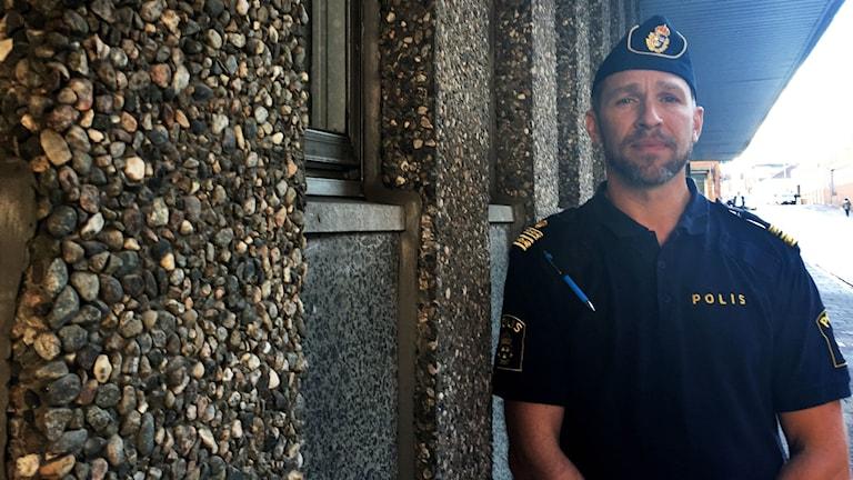 Tomas Stakeberg Jansson, lokalpolisområdeschef i Borås, står till höger i bild bredvid en vägg av murad småsten.