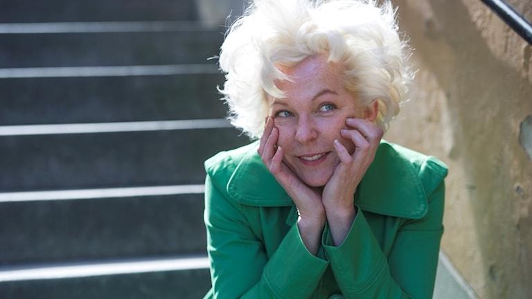 Porträttbild på blond Eva med grön kavaj.