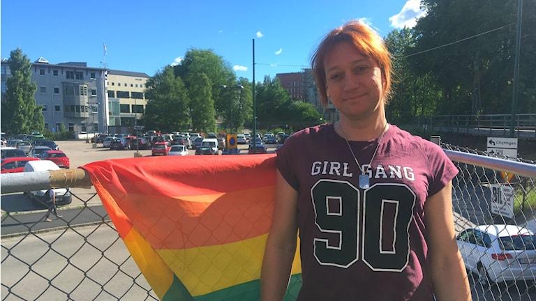 Emilia Larsdotter står till vänster i bild med en regnbågsflagga i bakgrunden.