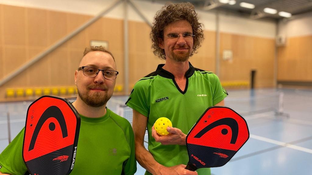 Två män i gröna tröjor håller i orangea rackets.