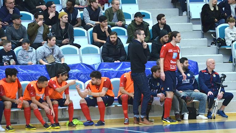 BAIK Futsal. Tränaren Petter Florentin stående i svart.