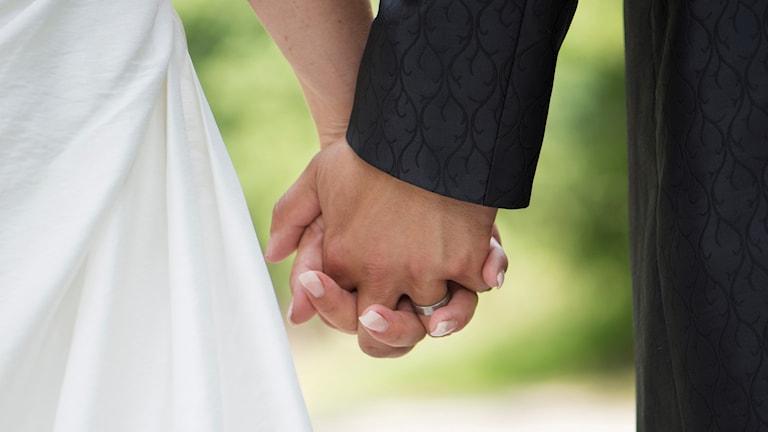 Ett brudpar håller varandra i hand.