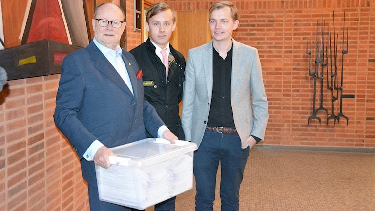Per-Olof Höög (S) håller en stor vit låda bredvid står Niklas Arvidsson (KD) och Marcus Nilsen(LUF)