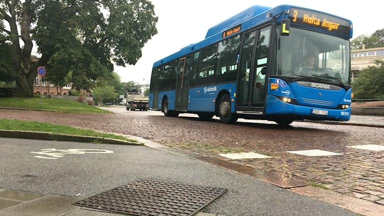 En blå västtrafikbuss kör på en regnblöt kullerstensgata i Borås.