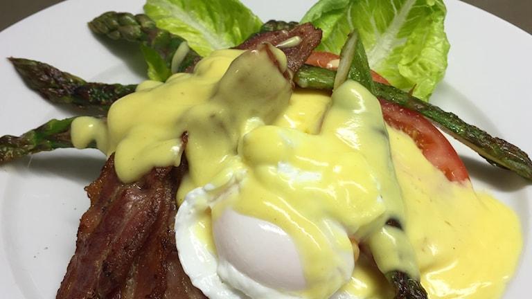 Pocherat ägg, bacon, sparris, tomatskivor, salladsblad och hollandaisesås på en smörgås.