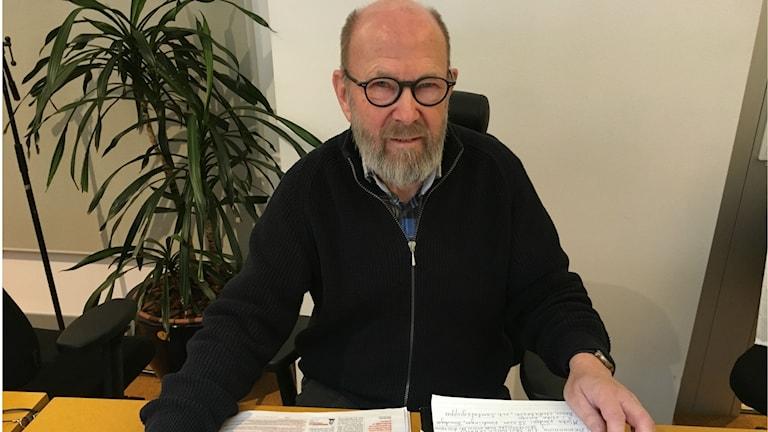 Arne Sjögren sitter vid ett skrivbord med en pärm framför sig.