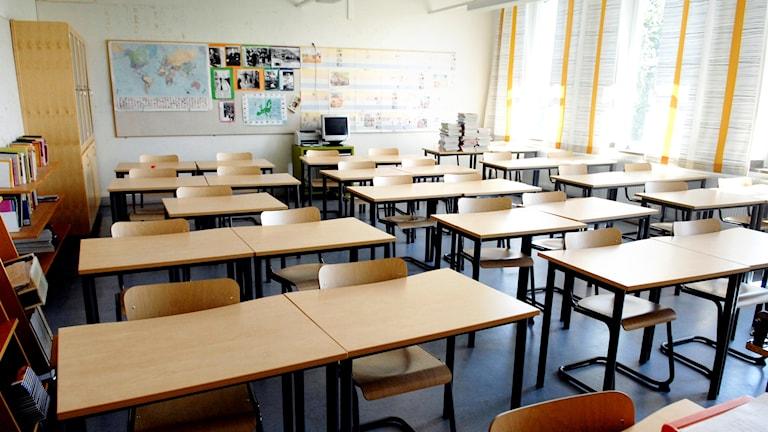 Ett klassrum med bänkar i rader.