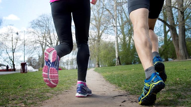 En kvinna och en man springer i träningskläder.