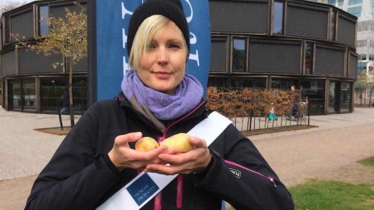 En kvinna står och håller två potatisar