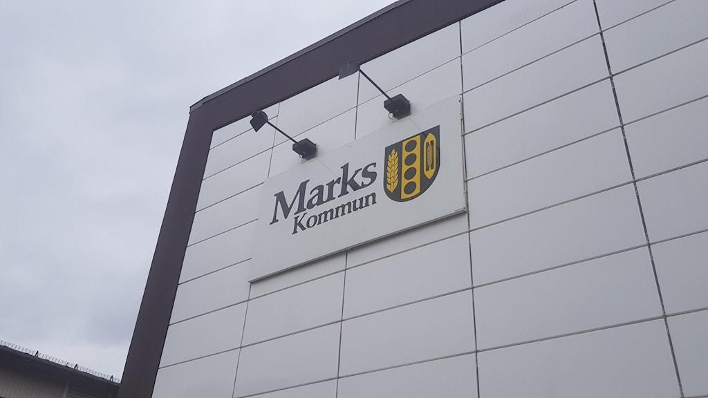 """En vit, stor byggnad med mörka knutar. En skylt på fasaden där det står """"Marks kommun"""" och en logga."""