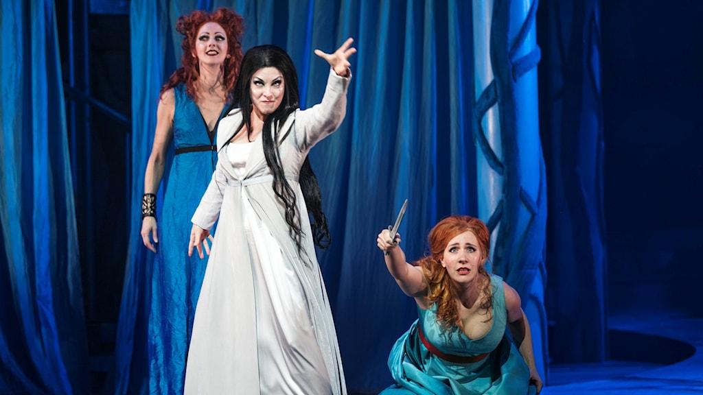 En kvinna i vit klänning sträcker ut armen. En annan kvinna sitrer på golvet med en kniv i handen. Bakom står två andra kvinnor i blåa klänningar.