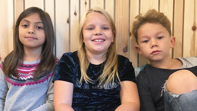 Barnen Eira Tönnberg, Bella Johansson och Theo Nause sitter mot en trävägg