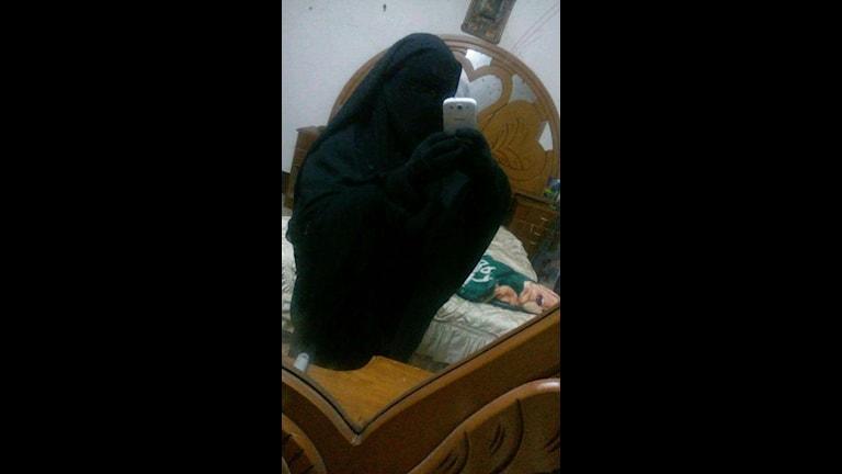 Marilyn Nevalainen sitter i en burka i en säng