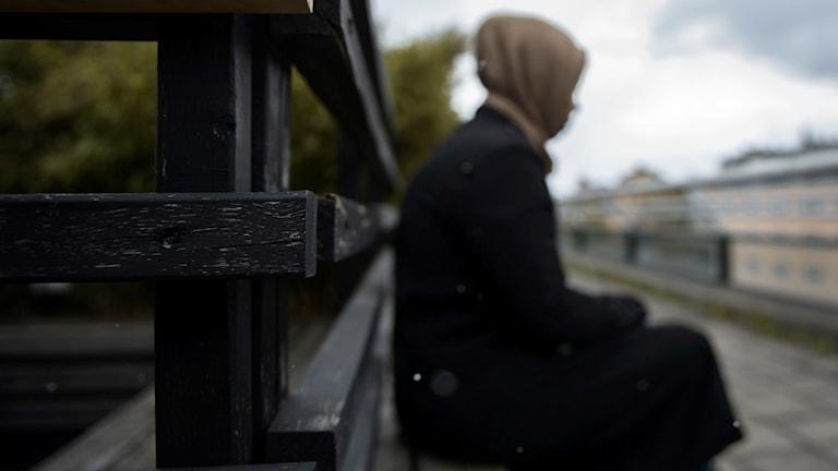 Kvinna sitter på en bänk med ett staket bakom sig.