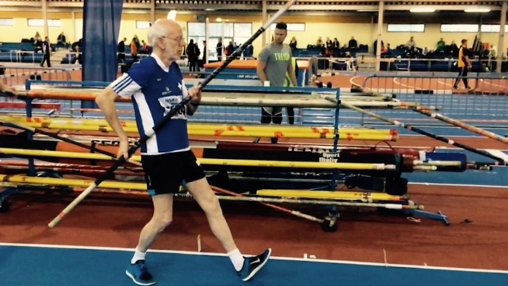 En man tar ett steg fram på en löparbana med en stav i händerna