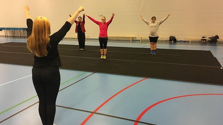 Mikael Nordlund, Louise Nilsson och Maja Jonsson tränar paracheer i Sjuhäradshallen under ledning av Moa Söderberg.