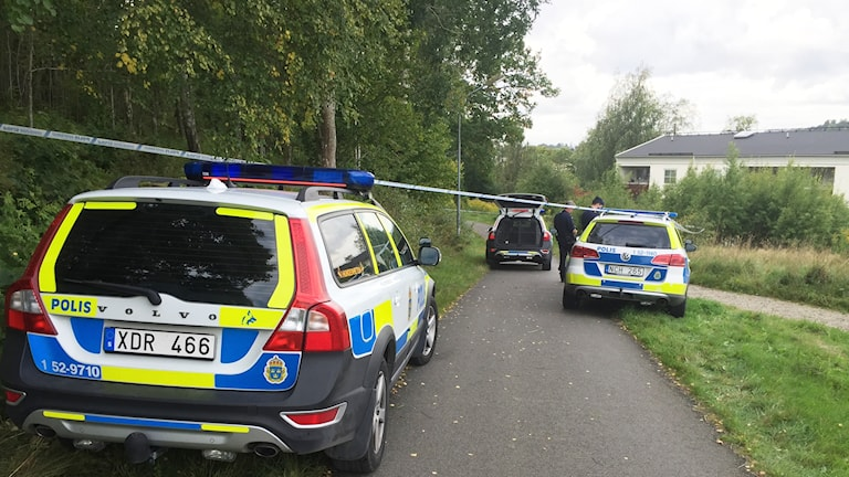 Polisbilar och avspärrning vid skogsparti bredvid skolan.
