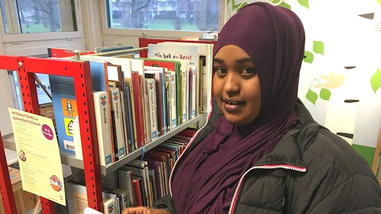 Hawalul Mohamed Hassan står framför en röd bokhylla med barnböcker.