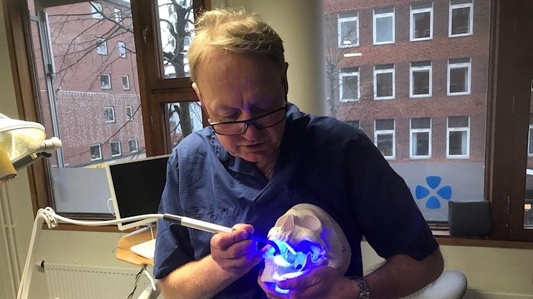 Tandläkare visar på plastskalle hur man lagar.