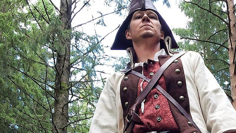 Henrik Mattsson i skogen klädd i sin karaktärs dräkt.